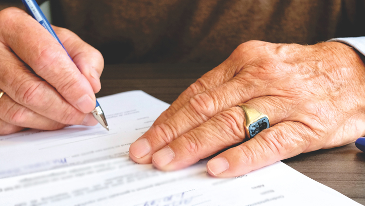 man signing legal document for house sale